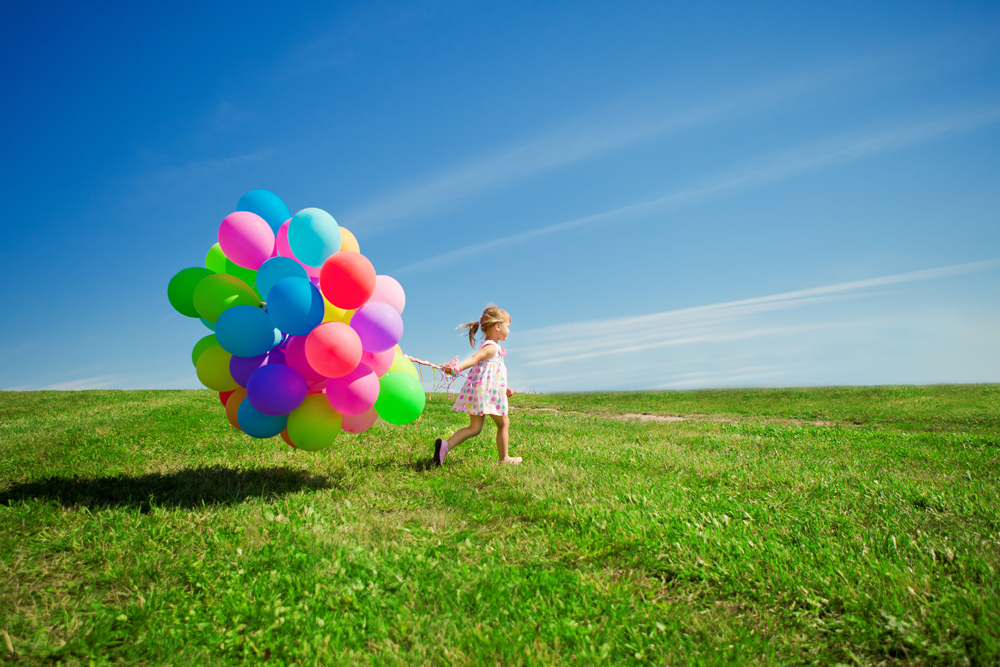 Little girl holding colorful balloons. Child playing on a green